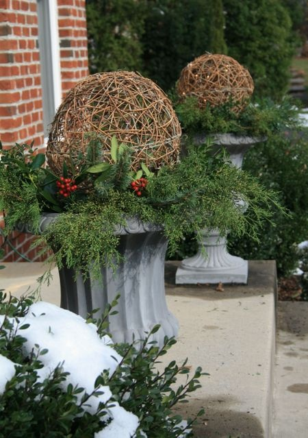 planters filled with greenery and lighted wicker balls